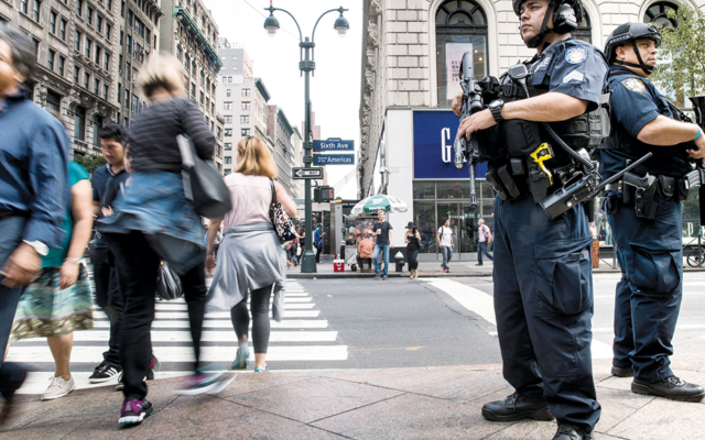 Members of the New York City Police Department stand guard in Herald Square in Manhattan on Sunday. It's near Chelsea, where a bomb was set off the night before. (Drew Angerer/Getty Images)