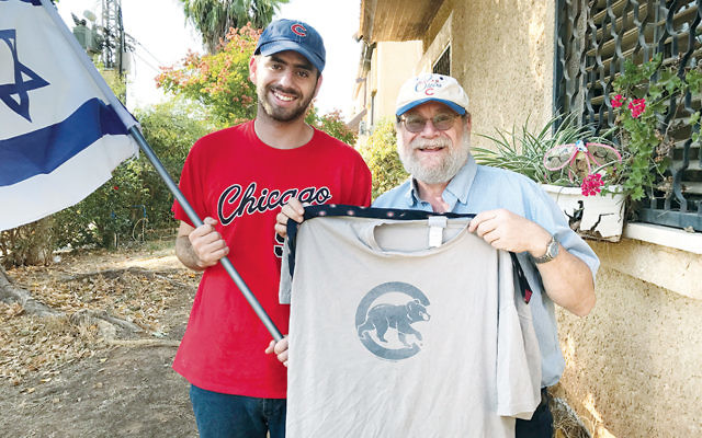 Harel Gold, left, and Rabbi Sidney Gold display their Cubs gear outside their West Bank home in Karnei Shomron. (Andrew Tobin)