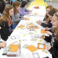 """Students at the Bergen County High School of Jewish Studies celebrated Sukkot by drinking lulav """"shakes,"""" playing Sukkot bingo, and decorating fall frames. Here, eighth-graders put photos into their frames. (Courtesy BCHSJS)"""