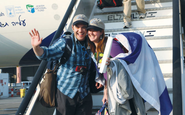 A couple making aliyah, wrapped in an Israeli flag, get off an El Al flight in 2014.