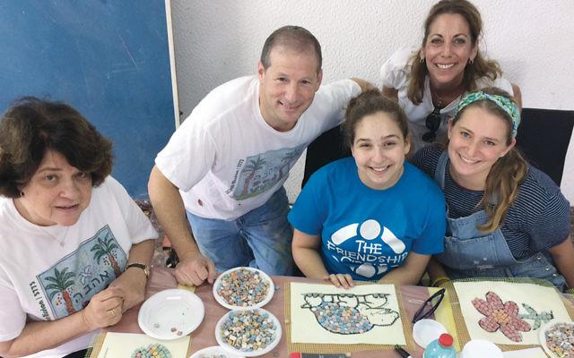 Gloria Brettner, Rabbi Craig Scheff, Mikalah Weinger, Leslee Schwartz, and Allison  Waldman create mosaics that will go on benchtops in Kfar Ahava's new garden, which the Orangetown Jewish Center is building.