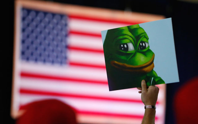 BEDFORD, NH - SEPTEMBER 28:  A Donald Trump supporter holds a cartoon designated a hate symbol by the anti-defamation league before the start of a campaign event in Bedford, NH, on Sept. 29, 2016.  (Photo by Jessica Rinaldi/The Boston Globe via Getty Images)