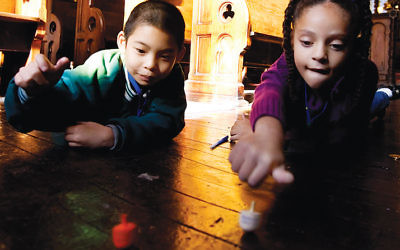 Kids spin dreidels at the Eldridge Street Synagogue on Manhattan's Lower East Side. The game of dreidel was inspired by a German game played at Christmastime. (Stephen Chernin/Getty Images)
