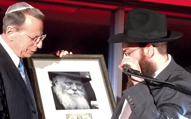 Steven Morey Greenberg accepts a framed picture of Rabbi Menachem Schnerson from Rabbi Shmary Gurary.