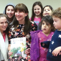 """Children surround author Leah Escott after she read her new book, """"Rosey Raises Roses,"""" at the Bergenfield Public Library. The illustrated book includes topics about career choices, destiny, and tradition. Leah, her husband, Reuven, and four children are longtime members of Congregation Beth Abraham in Bergenfield and active members of the Bergenfield/Teaneck Jewish community. (Photo provided)"""