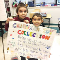 "As part of Sinai Schools' speech/language therapy program, the children in Sinai's program at the Rosenbaum Yeshiva of North Jersey have a monthly ""Giver's Club"" meeting, where they plan chesed activities. Students in the 2S class chose a Chanukah toy drive as their first project of the year. They worked in small groups to make posters and have begun to collect toys, which they will deliver to the children's ward of a local hospital. (Courtesy Sinai)"