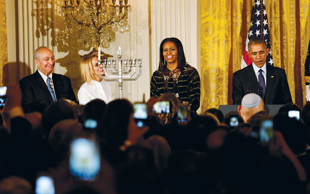 President Barack Obama, with his wife, Michelle, speaks at a Chanukah reception with the son and granddaughter of the late Israeli President Shimon Peres — Chemi Peres, left, and Mika Almog — at the White House on December 14. (Aude Guerrucci-pool/Getty Images)