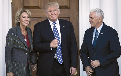 Betsy DeVos, President-elect Donald Trump, and Vice President-elect Mike Pence outside the clubhouse at Trump International Golf Club in Bedminster Township. (Drew Angerer/Getty Images)