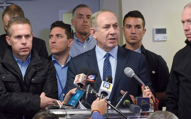 Prime Minister Benjamin Netanyahu, surrounded by security and government officials, talks about the fires at a briefing in Haifa on November 24. (Amos Ben Gershom/Israeli Government Press Office)