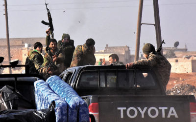 Pro-government forces fire ammunition as Syrians arrive in Jibrin on the eastern outskirts of Aleppo on December 19. (George Ourfalian/AFP/Getty Images)