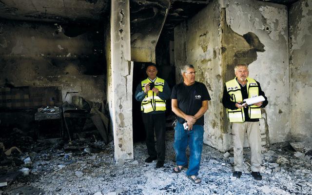 Israelis inspect the damage to a burnt house in Haifa on November 25. (Gili Yaari/Flash90)