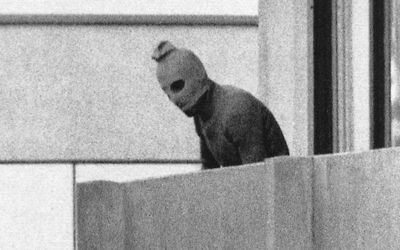 A Black September terrorist looks out from a terrace; the doomed Israelis athletes are held hostage in the apartment behind him.
