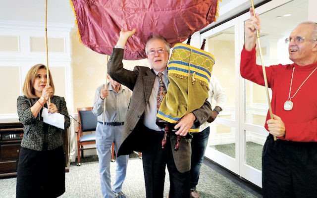From left, are the Jewish Home Family's president and CEO, Carol Silver Elliott; Rabbi Dr. Ari Korenblit, and two residents dancing the Torah scroll to its new ark.