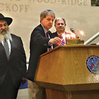 Ron Rosensweig, center, chair of the Jewish Federation Community Relations Committee, lights a candle at Bergen County's annual menorah lighting ceremony as Rabbi Mordecai Kanefsky of Bris Avrohom, left, and James Tedesco, Bergen County Executive, watch. (Courtesy Federation)