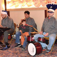 """The Jewish Center of Teaneck's """"Menorah Men"""" — keyboardist Josh Levine, trumpeter Amir Cohen, and drummer Jonathan Resnick — performed at the shul's Chanukah community youth party. Levine's and Resnick's sons are shown with them. Meredith Levine chaired the party committee. (Michael Laves)"""
