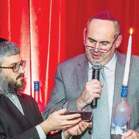 Bris Avrohom of Fair Lawn offered Chanukah Night Live, a party for adults. Rabbi Mendel Zaltzman, left, lit the Grey Goose menorah with Alex Buz of Ridgewood. (Courtesy Bris Avrohom)