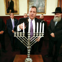 New Jersey Governor Chris Christie lit the shamash candle at a fifth-day Chanukah ceremony in the Trenton Statehouse. Mark Levenson, N.J. Israel Commission chair, and Rabbis Shmuley Boteach of Englewood and Steven Pruzansky of Teaneck also attended. (Courtesy Chabad)