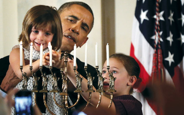 President Barack Obama holds Kylie Schmitter, 4, to light a menorah as Kylie's sister Lainey looks on during a Chanukah reception at the White House in 2013. (Alex Wong/Getty Images)