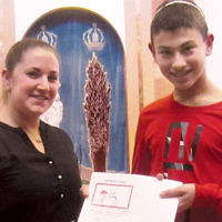 Rebekah Adelson, the Jewish National Fund's Israel Programs admissions director, receives letters from Shomrei Torah sixth grader Noah Golden. He and his classmates wrote notes of encouragement to Israeli firefighters who fought the recent widespread fires in Israel. (Courtesy ST)