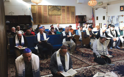 It is a custom among Karaite Jews to pray kneeling on the ground, as seen here in the sanctuary of Congregation B'nai Israel in Daly City, Calif. (Courtesy of Karaite Jews of America)