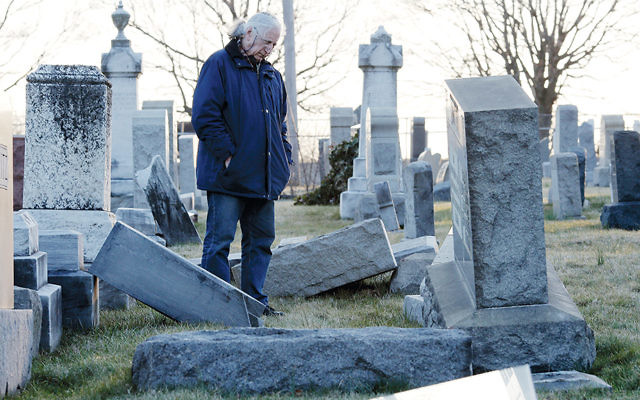 A visitor to the vandalized Jewish Mount Carmel Cemetery in Philadelphia looks at some of the toppled tombstones on February 26. (Dominick Reuter/AFP/Getty Images)