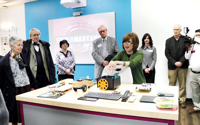 Benjamin Yalow, second from left, looks on as STEAM instructor Reyce Krause shows off Ma'ayanot's Makerspace.