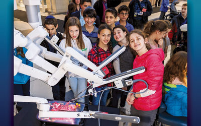 Sixth graders from Solomon Schechter Day School of Bergen County gather around the da Vinci surgical system at Englewood Hospital and Medical Center.