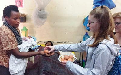 Sarah Miller hands an egg and a pint of milk to a Rwandan mother who recently gave birth in a maternity hospital in Kigali. (Photos courtesy of the Miller family)