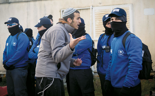 An Israeli settler argues with police officers evacuating a West Bank outpost, Amona, on February 1. (Miriam Alster/Flash90)