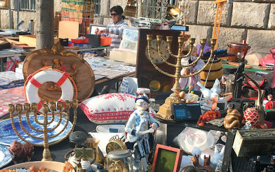 Two Chanukah menorahs sit amid a jumble of antiques at a flea market in Berlin. (Orit Arfa)