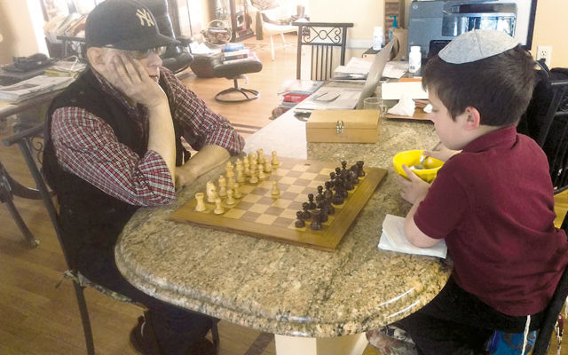 Jack Flamholz teaches chess to one of his grandsons. (Flamholz family)