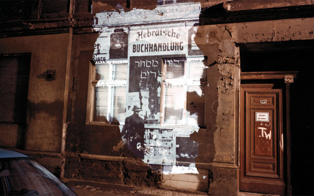 "Almstadtstrasse 43 (formerly Grenadierstrasse 7): Slide projection of former Hebrew bookstore, 1930, Berlin, shown in 1992, 33"" x 40"" chromogenic photograph and on-location installation by Shimon Attie (Courtesy of Jack Shainman Gallery, New York)"