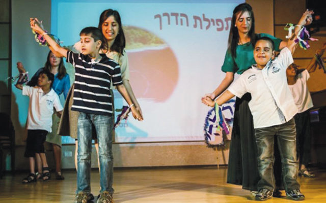 Teachers at the Jerusalem Institute for the Blind help students with dancing and exercise movements.