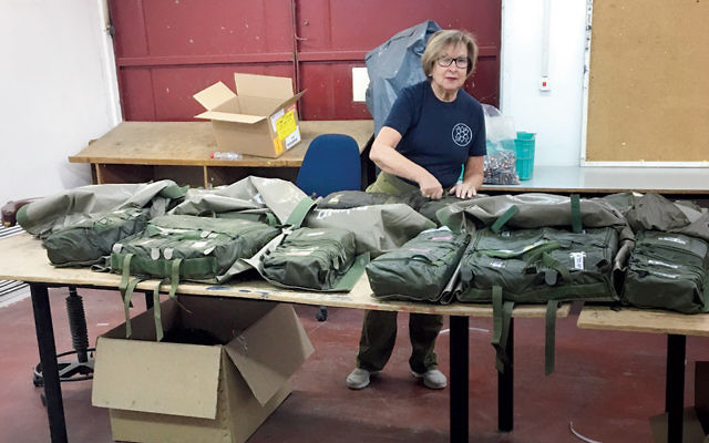 Hilda Froelke stands with some of the medical backpacks she assembled on an IDF supply base.