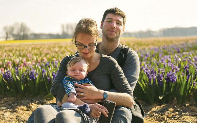 Cnaan Liphshiz, his wife, Iris, and their older son, Ilai, sit in a tulip field near Amsterdam in 2016. (Courtesy of Cnaan Liphshiz)