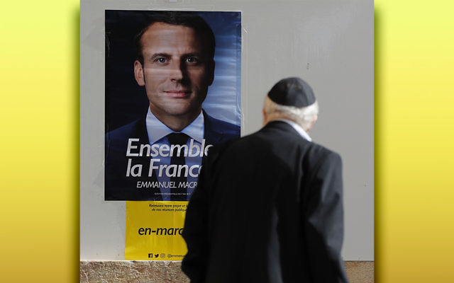 A man looks at an Emmanuel Macron poster at the French consulate in Jerusalem. (Thomas Coex/AFP/Getty Images)