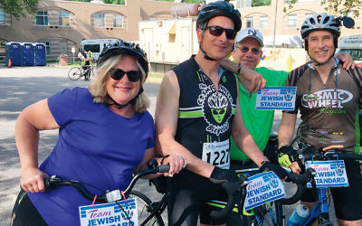 Jewish Standard riders Beth Chananie, Jamie Janoff, and Jerry Szubin are ready to go; Beth's husband, Rob Chananie, stands behind to cheer them on.