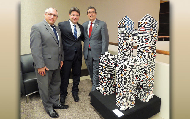 Israel Deputy Consul General for New York Amir Sagie, left, Ofir Akunis, Israel's Minister of Science, Technology, and Space, and Mark Levenson, chair of the New Jersey Israel Commission stand next to the Empire State Chair, a project of the WAE center of the Jewish Service for the Developmentally Disabled, which Eta and Mark Levenson bought for the Eric Eliezer Levenson Foundation for Hope. It is now on display at the law offices of Sills Cummis & Gross in Newark.