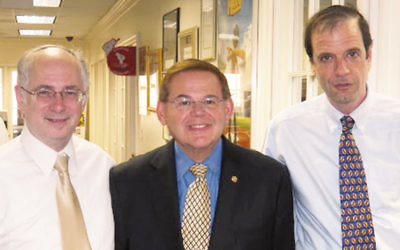 Host committee members Ben Chouake, left, and  Howard Jonas flank Senator Robert Menendez.