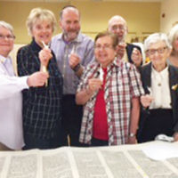 Rabbi Kenneth Stern, back row left, and sofer Rabbi Jay Greenspan, next to him, are with congregants who gathered to help repair the Torah scrolls at Congregation Gesher Shalom/JCC Fort Lee. (Photo provided)