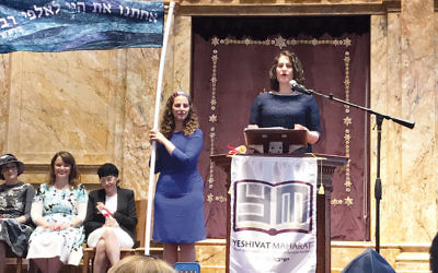 Rabba Eryn London speaks at her ordination; three of the four other newly ordained Maharat graduates — from left, Rabbanit Chava Evans, Rabbanit Goldie Guy, and Rabbanit Bracha Jaffe listen. Rabbi Lila Kagedan, who was ordained in 2015, holds the pole.