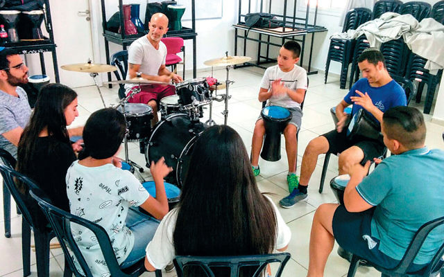 Rafael Anapolle, left, and his students at a drum workshop.