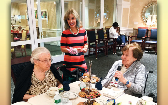 Carol Silver Elliott hands the microphone to a resident at a celebration at the Jewish Home Assisted Living in River Vale. (Jewish Home Family)
