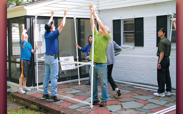 Safely@Home volunteers help erect a sukkah. (Courtesy Jewish Home Family)