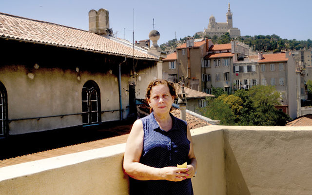 Martine Yana, director of the Edmond Fleg Center in Marseille, France, stands on the center's terrace roof in July. (Cnaan Liphshiz)