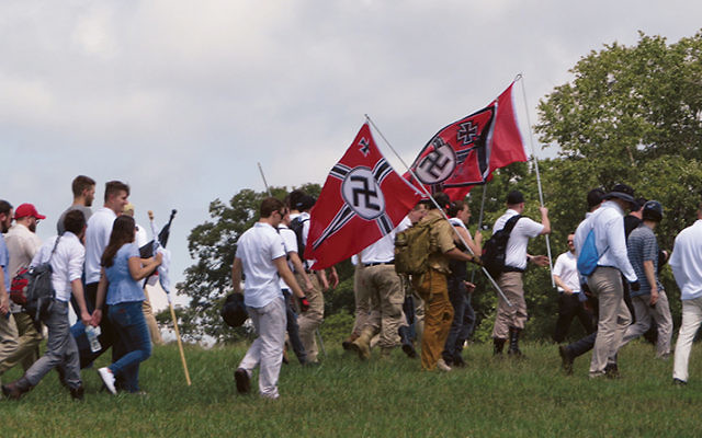 White supremacists carry Nazi flags.