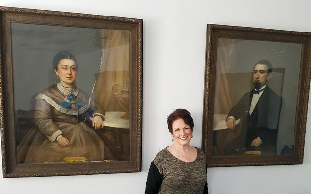 Bonnie Barnert stands between pictures of her ancestors at the Jewish Historical Society of North Jersey (Courtesy JHNJ)