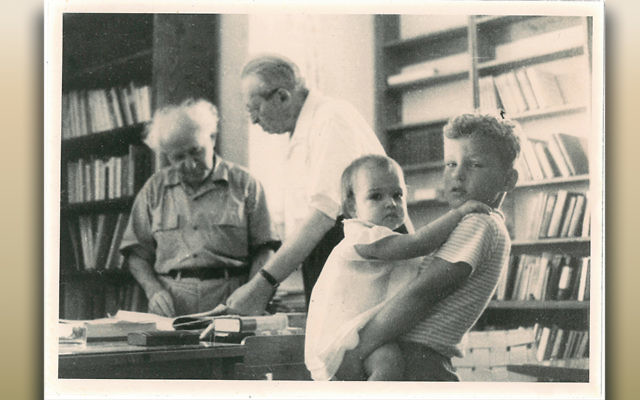 Alon Ben-Gurion holds his baby sister as his grandfather works in his study, sometime in the late 1950s.