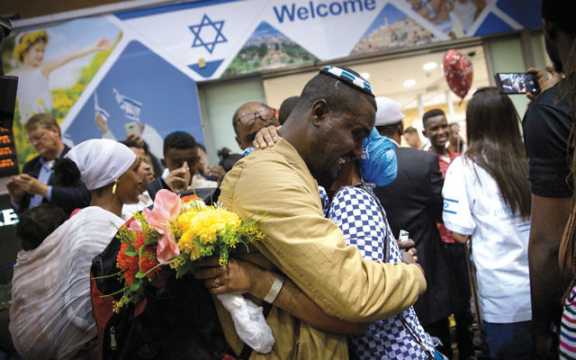 Family members greet Ethiopian Jews who arrive at Israel's Ben Gurion Airport as they make aliyah in June 2017. (Miriam Alster/Flash90)
