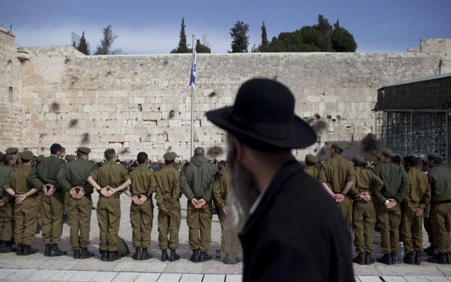 A haredi Orthodox man watching Israeli soldiers at an army ceremony at the Western Wall in Jerusalem, Feb. 22, 2012. (Yonatan Sindel/FLASH90/JTA)